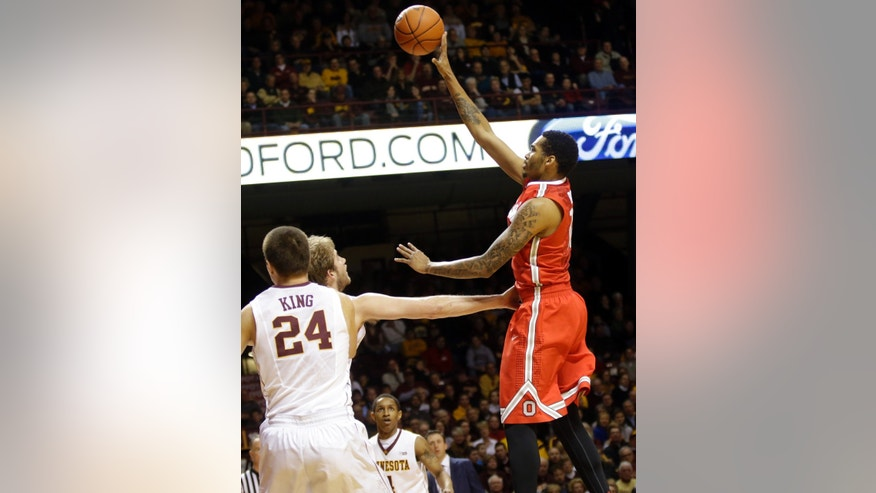 Ohio State's LaQuinton Ross, right, shoots over Minnesota's Elliott Eliason and Joe King (24) in the first half of an NCAA college basketball game, Thursday, Jan. 16, 2014, in Minneapolis. (AP Photo/Jim Mone)