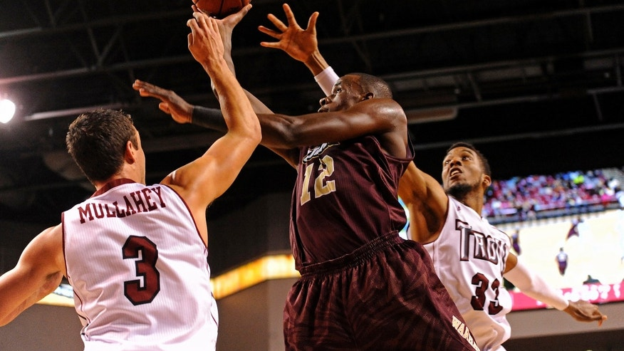 Louisiana-Monroe forward Tylor Ongwae (12) goes up to shoot past Troy guard Jeff Mullahey (3) and forward/center Westley Hinton (33) during the second half of an NCAA college basketball game in Troy, Ala., Thursday, Jan. 16, 2014. Louisiana-Monroe won 75-64. (AP Photo/The (Troy) Messenger, Thomas Graning)