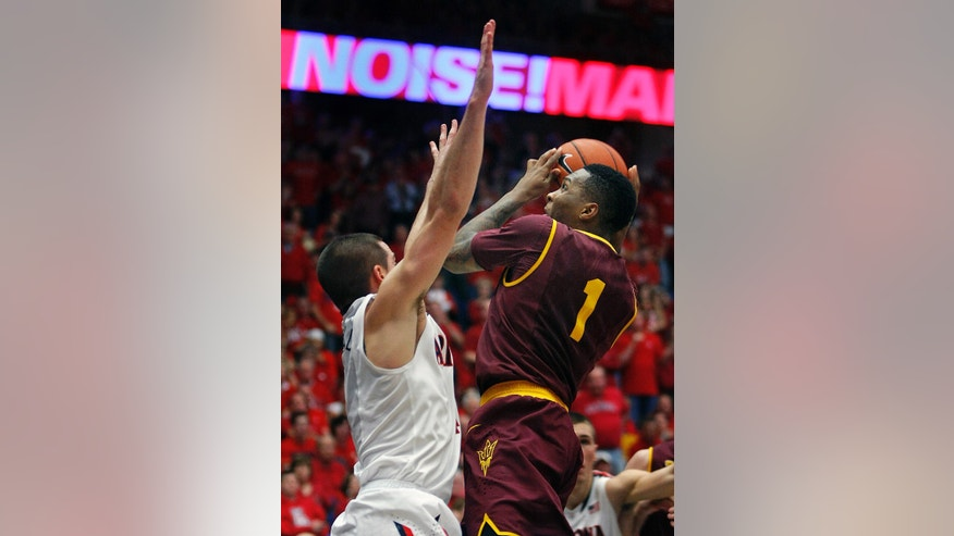 Arizona State's Jahil Carson (1) shoots over Arizona's T.J. McConnell during the second half of an NCAA college basketball game Thursday, Jan. 16, 2014, in Tucson, Ariz. Arizona won 91-68. (AP Photo/John MIller)