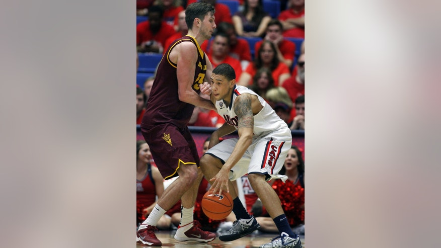 Arizona's Brandon Ashley, right, drives for a shot against the defense of Arizona State's Jordan Bachynski, left, in the second half of an NCAA college basketball game on Thursday, Jan. 16, 2014, in Tucson, Ariz. Arizona won 91-68. (AP Photo/John MIller)
