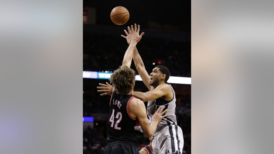 San Antonio Spurs' Tim Duncan, right, shoots over Portland Trail Blazers' Robin Lopez (42) during the first half on an NBA basketball game, Friday, Jan. 17, 2014, in San Antonio. (AP Photo/Eric Gay)