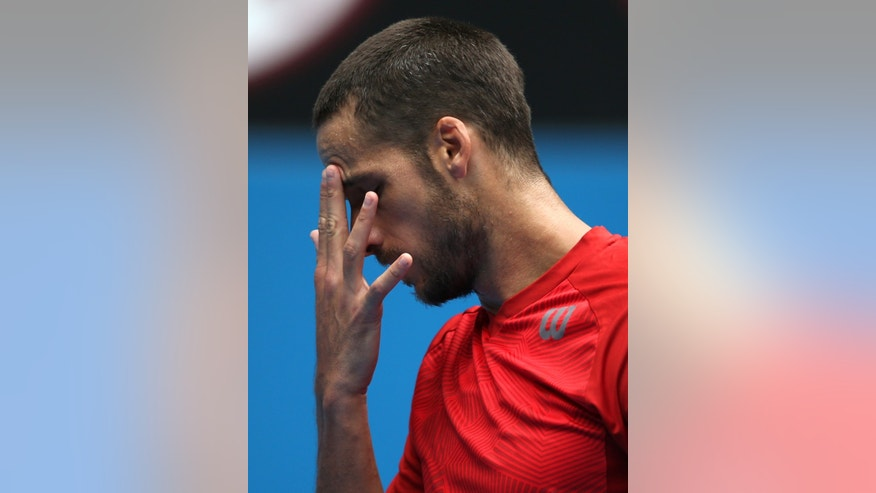 Feliciano Lopez of Spain touches his brows between points as he plays Andy Murray of Britain during their third round match at the Australian Open tennis championship in Melbourne, Australia, Saturday, Jan. 18, 2014.(AP Photo/Rick Rycroft)