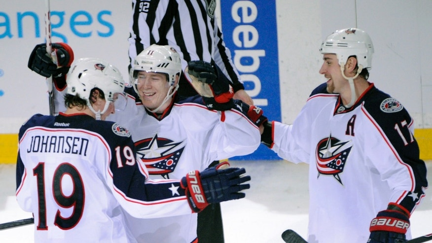 Columbus Blue Jackets Ryan Johansen (19) celebrates with Matt Calvert, center, and Brandon Dubinsky (17) after Johansen scored the game-winning goal during a shootout in an NHL hockey game against the Buffalo Sabres in Buffalo, N.Y., Saturday, Jan.18, 2014. Columbus won 4-3. (AP Photo/Gary Wiepert)
