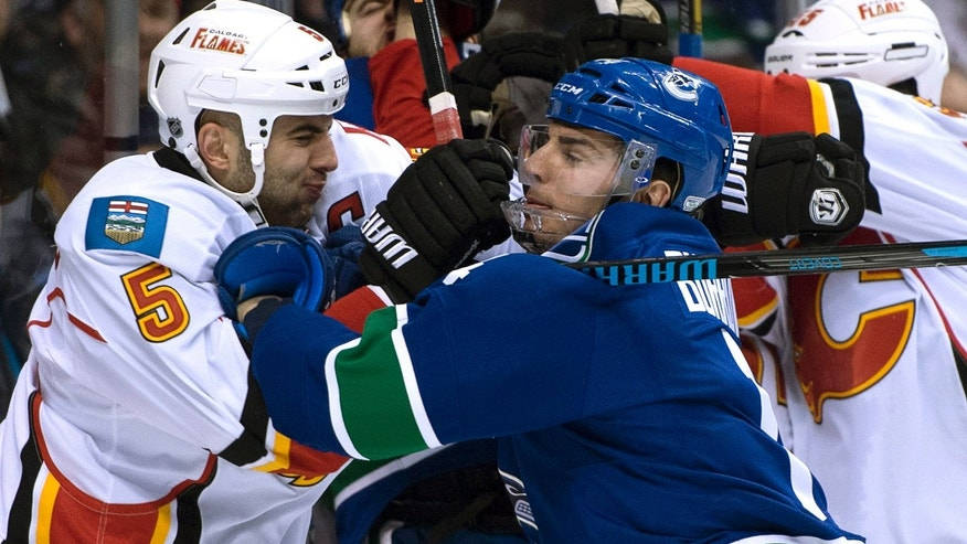 Vancouver Canucks left wing Alex Burrows (14) wrestles with Calgary Flames defenseman Mark Giordano (5) during the first period of NHL hockey game action in Vancouver, British Columbia, Saturday, Jan. 18, 2014. (AP Photo/The Canadian Press, Jonathan Hayward)