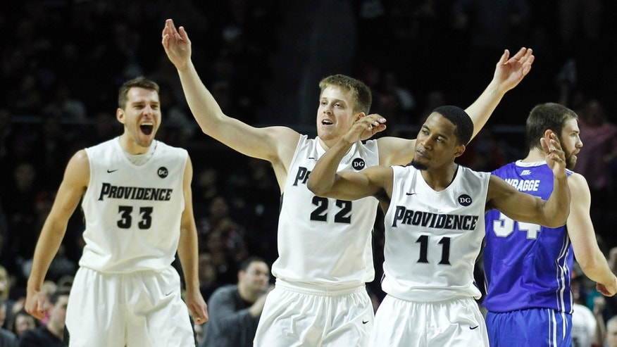 Providence forward Carson Desrosiers (33) guard Ted Bancroft (22) and guard Bryce Cotton (11) celebrate their lead during the second half of an NCAA college basketball game against Creighton, Saturday, Jan. 18, 2014, in Providence, R.I.  Providence defeated Creighton 81-68.(AP Photo/Stew Milne)