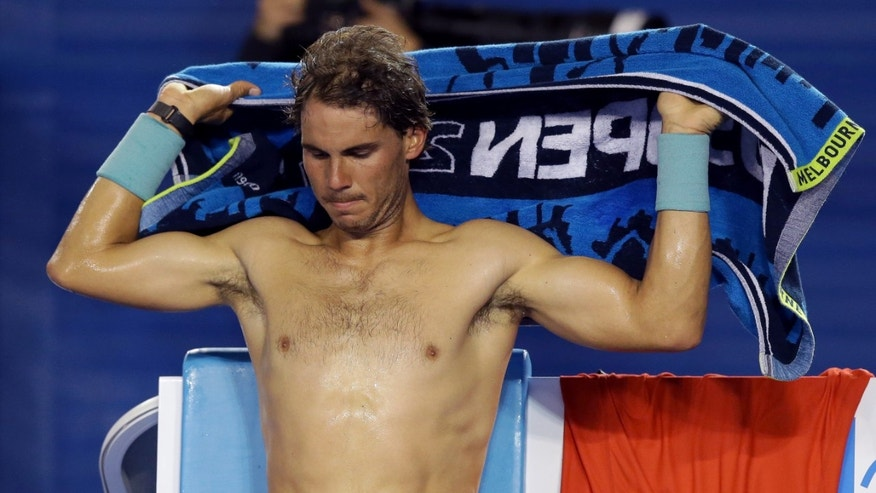 Rafael Nadal of Spain dries his body with a towel during a break in his third round match against  Gael Monfils of France  at the Australian Open tennis championship in Melbourne, Australia, Saturday, Jan. 18, 2014.(AP Photo/Aaron Favila)