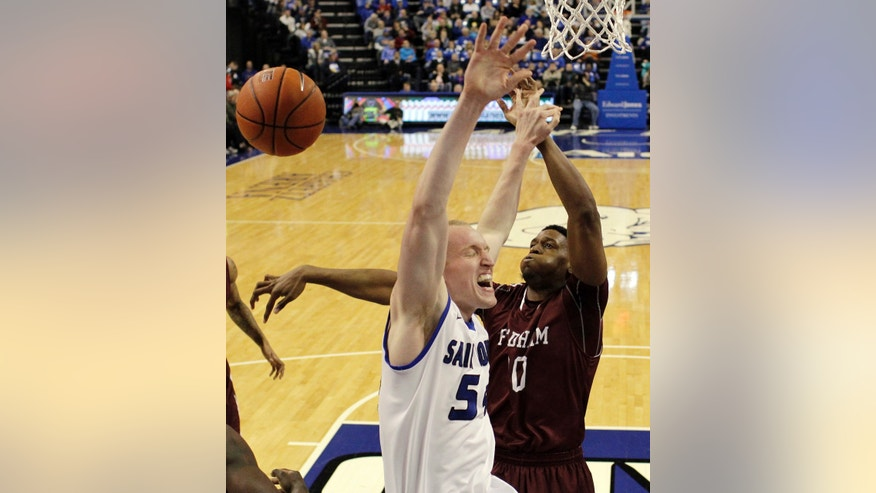 Saint Louis' John Manning, left, is fouled on his way to the basket by Fordham's Ryan Rhoomes during the first half of an NCAA college basketball game Saturday, Jan. 18, 2014, in St. Louis. (AP Photo/Jeff Roberson)