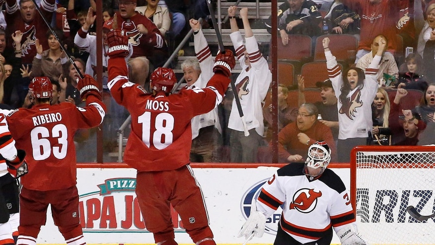 Phoenix Coyotes' David Moss (18) and Mike Ribeiro (63) celebrate a goal scored by teammate Jeff Halpern against New Jersey Devils' Martin Brodeur, right, during the first period of an NHL hockey game on Saturday, Jan. 18, 2014, in Glendale, Ariz. (AP Photo/Ross D. Franklin)