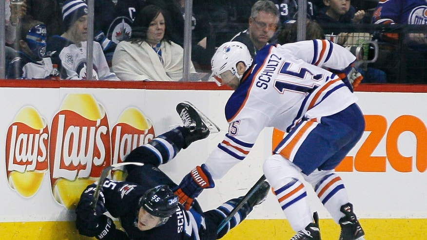 Edmonton Oilers' Nick Schultz (15) checks Winnipeg Jets' Mark Scheifele (55) during the second period of an NHL hockey game in Winnipeg, Manitoba, Saturday, Jan. 18, 2014. (AP Photo/The Canadian Press, John Woods)
