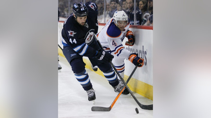 Winnipeg Jets' Zach Bogosian (44) and Edmonton Oilers' Taylor Hall (4) battles for the puck during the second period of an NHL hockey game in Winnipeg, Manitoba, Saturday, Jan. 18, 2014. (AP Photo/The Canadian Press, John Woods)