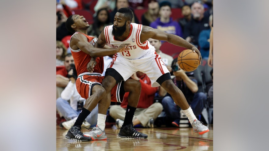 Milwaukee Bucks' Brandon Knight, left, falls backward after making contact with Houston Rockets' James Harden (13) during the first quarter of an NBA basketball game, Saturday, Jan. 18, 2014, in Houston. Knight was called for a foul. (AP Photo/David J. Phillip)