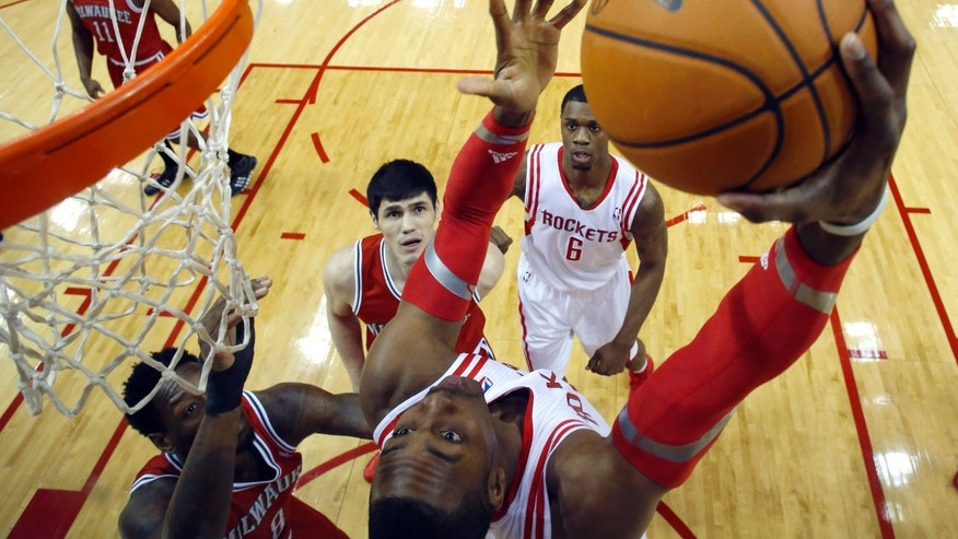 Houston Rockets' Dwight Howard, right, looks back to shoot as Milwaukee Bucks' Larry Sanders (8) defends during the first quarter of an NBA basketball game, Saturday, Jan. 18, 2014, in Houston. (AP Photo/David J. Phillip)
