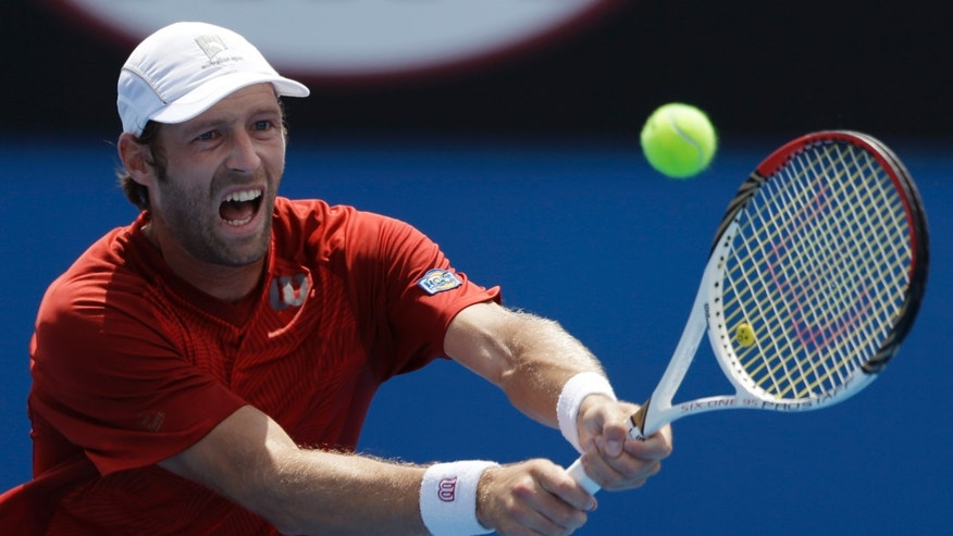 Stephane Robert of France makes backhand return to Martin Klizan of Slovakia during their third round match at the Australian Open tennis championship in Melbourne, Australia, Saturday, Jan. 18, 2014.(AP Photo/Aijaz Rahi)