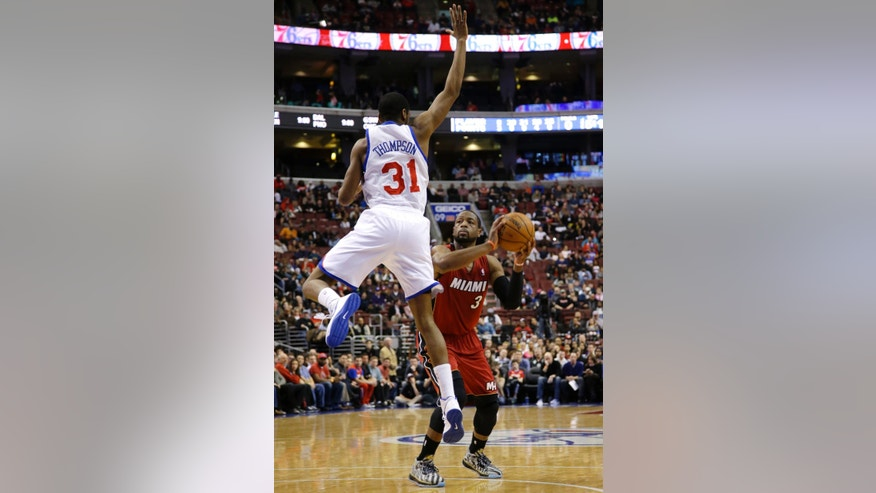 Miami Heat's Dwyane Wade (3) prepares to shoot against Philadelphia 76ers' Hollis Thompson (31) during the first half of an NBA basketball game on Friday, Jan. 17, 2014, in Philadelphia. (AP Photo/Matt Slocum)