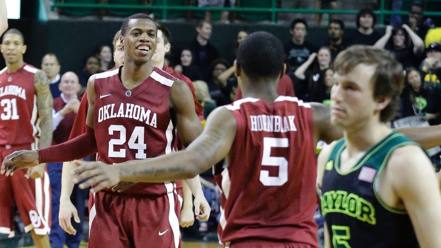 Oklahoma guard Je'lon Hornbeak (5) heads over to celebrate with teammate Buddy Hield (24) as Baylor guard Brady Heslip (5) walks off the court after an NCAA college basketball game Saturday, Jan. 18, 2014, in Waco, Texas. Oklahoma won 66-64. (AP Photo/LM Otero)