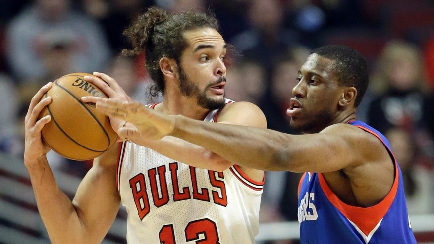 Chicago Bulls center Joakim Noah (13) looks to a pass as Philadelphia 76ers forward Thaddeus Young, right, guards during the first half of an NBA basketball game in Chicago, Saturday, Jan. 18, 2014. (AP Photo/Nam Y. Huh)