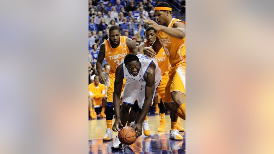 Kentucky's Julius Randle, bottom, tries to gather up the ball near, from left, Tennessee's Jeronne Maymon, Josh Richardson, and Jarnell Stokes during the first half of an NCAA college basketball game, Saturday, Jan. 18, 2014, in Lexington, Ky. (AP Photo/James Crisp)