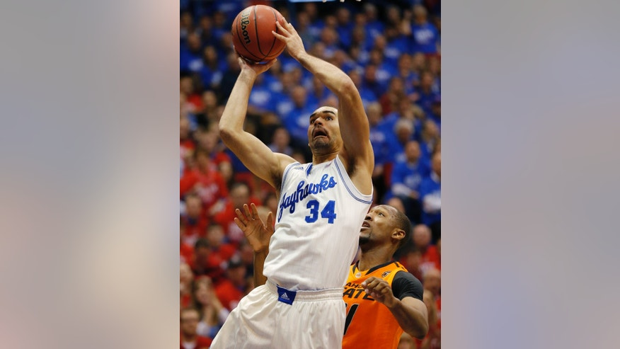 Kansas forward Perry Ellis (34) shoots while covered by Oklahoma State forward/center Kamari Murphy (21) during the first half of an NCAA college basketball game at Allen Fieldhouse in Lawrence, Kan., Saturday, Jan. 18, 2014. (AP Photo/Orlin Wagner)