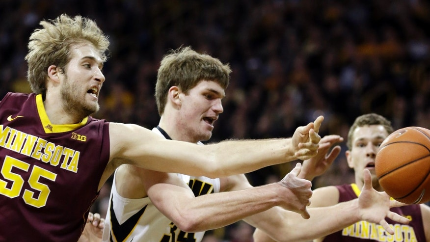 Iowa center Adam Woodbury, center, fights for a rebound with Minnesota's Elliott Eliason, left, and Oto Osenieks, right, during the first half of an NCAA college basketball game on Sunday, Jan. 19, 2014, in Iowa City, Iowa. (AP Photo/Charlie Neibergall)