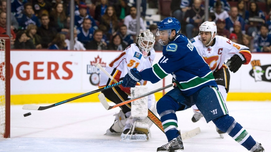 Calgary Flames goalie Karri Ramo (31) and defenseman Mark Giordano (5) watch as Vancouver Canucks left wing Alex Burrows (14) misses a shot during the first period of an NHL hockey game Saturday, Jan. 18, 2014, in Vancouver, British Columbia. (AP Photo/The Canadian Press, Jonathan Hayward)