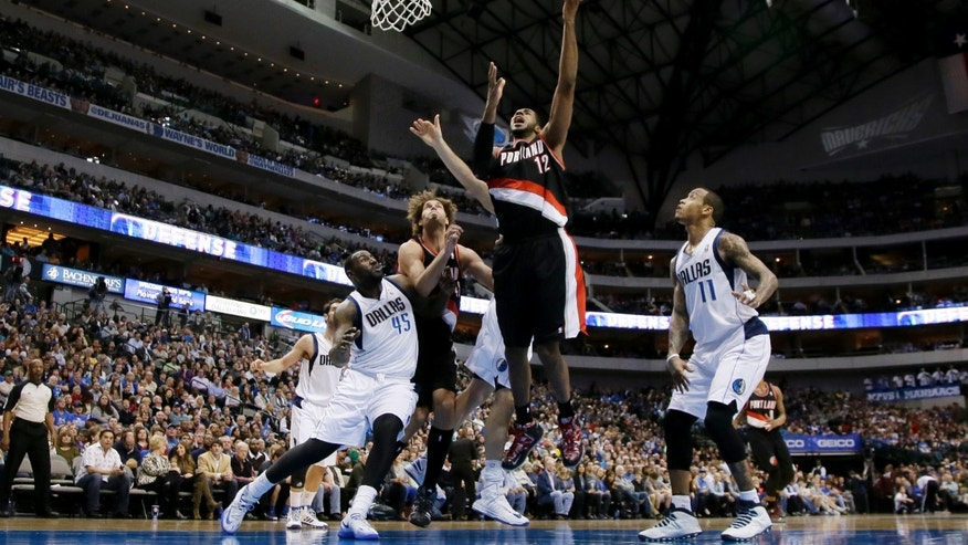 Portland Trail Blazers power forward LaMarcus Aldridge, center, goes up for a shot as Dallas Mavericks' DeJuan Blair (45) and Monta Ellis (11) defend during the first half of an NBA basketball game, Saturday, Jan. 18, 2014, in Dallas. (AP Photo/Tony Gutierrez)