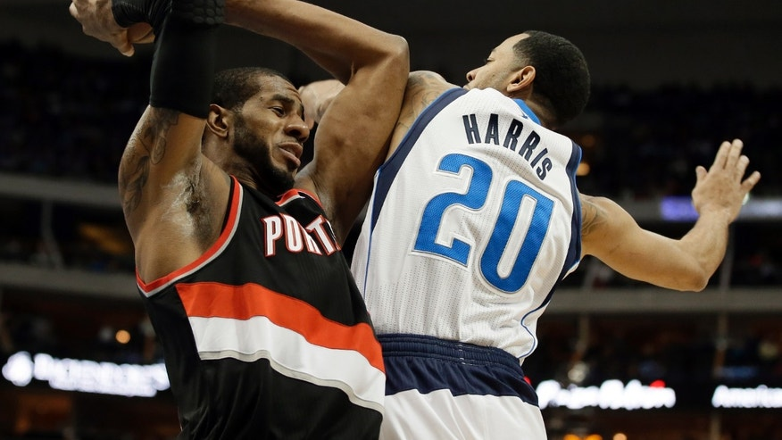 Portland Trail Blazers forward LaMarcus Aldridge, left, grabs an offensive rebound in front of Dallas Mavericks' Devin Harris (20) during the first half of an NBA basketball game, Saturday, Jan. 18, 2014, in Dallas. (AP Photo/Tony Gutierrez)