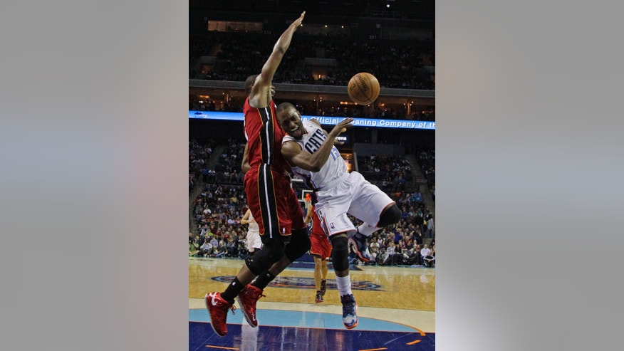 Charlotte Bobcats' Kemba Walker, right, loses the ball as he drives against Miami Heat's Chris Bosh, left, during the second half of an NBA basketball game in Charlotte, N.C., Saturday, Jan. 18, 2014. Walker was injured on the play. The Heat won 104-96 in overtime. (AP Photo/Chuck Burton)