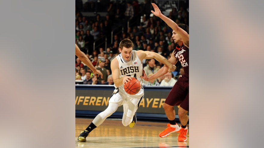 Notre Dame guard Pat Connaughton, left, drives the lane as Virginia Tech guard Christian Beyer defends during the first half of an NCAA college basketball game, Sunday, Jan. 19, 2014 in South Bend, Ind. (AP Photo/Joe Raymond)