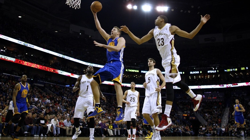 Golden State Warriors power forward David Lee, front left, drives to the basket past New Orleans Pelicans power forward Anthony Davis (23), point guard Tyreke Evans (1) and center Jeff Withey (5)during the first half of an NBA basketball game in New Orleans, Saturday, Jan. 18, 2014. (AP Photo/Jonathan Bachman)