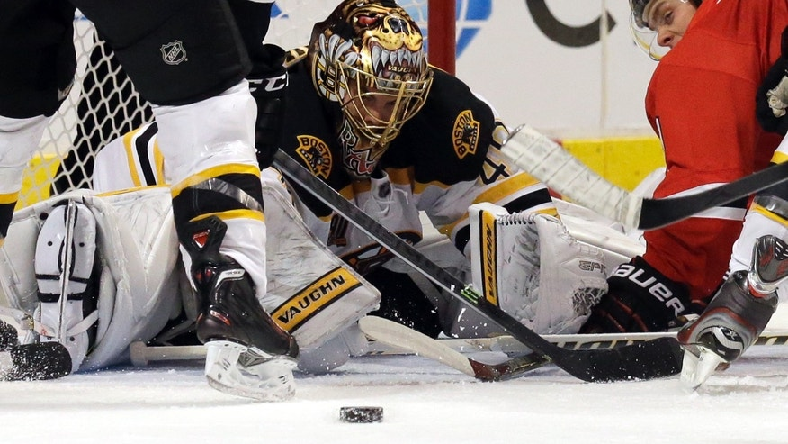Boston Bruins goalie Tuukka Rask (40) blocks a shot by Chicago Blackhawks' Jonathan Toews, right, during the second period of an NHL hockey game in Chicago, Sunday, Jan. 19, 2014. (AP Photo/Nam Y. Huh)