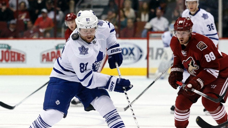 Toronto Maple Leafs right wing Phil Kessel (81) carries the puck past Phoenix Coyotes left wing Mikkel Boedker (89) in the first period of an NHL hockey game, Monday, Jan. 20, 2014, in Glendale, Ariz. (AP Photo/Rick Scuteri)