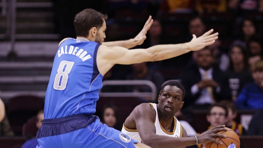 Cleveland Cavaliers' Loul Deng, right, from Sudan, looks for help under pressure from Dallas Mavericks' Jose Calderon, left, from Spain, during the first quarter of an NBA basketball game Monday, Jan. 20, 2014, in Cleveland. (AP Photo/Tony Dejak)