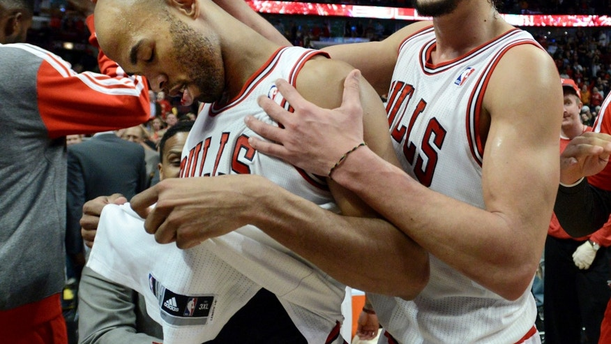 Chicago Bulls' Joakim Noah right, celebrates with teammate Taj Gibson left, after Gibson made the game-winning shot in overtime to defeat the Los Angeles Lakers 102-100 during an NBA basketball game in Chicago, Monday, Jan. 20, 2014. (AP Photo/Paul Beaty)
