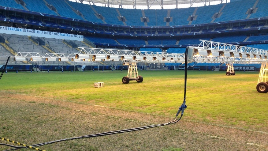 In this photo taken on Dec. 15, 2013, giant lighting rigs pictured,  helping to grow the reseeded pitch, at the new Gremio Arena, in the southern Brazilian city of Porto Alegre, which will be a training venue during the World Cup.  At Arsenal's Highbury Stadium, Edu played on one of football's finest pitches. Award-winning Arsenal groundsman Paul Burgess became so well-known for his green fingers that he was eventually lured away by Real Madrid. So when Edu returned home to Brazil in 2009 to finish his career, the worn and sorry state of some Brazilian football fields was an eye-opener. Even now, as the World Cup host rushes to ready itself, Edu says pitches in Brazil aren't on a par with those in Europe, where he played for eight years, at Arsenal and Valencia. (AP Photo/John Leicester)