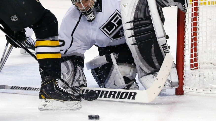 Los Angeles Kings goalie Jonathan Quick (32) keeps his eyes on the puck while protecting the net during the second period of an NHL hockey game against the Boston Bruins in Boston Monday, Jan. 20, 2014. (AP Photo/Elise Amendola)