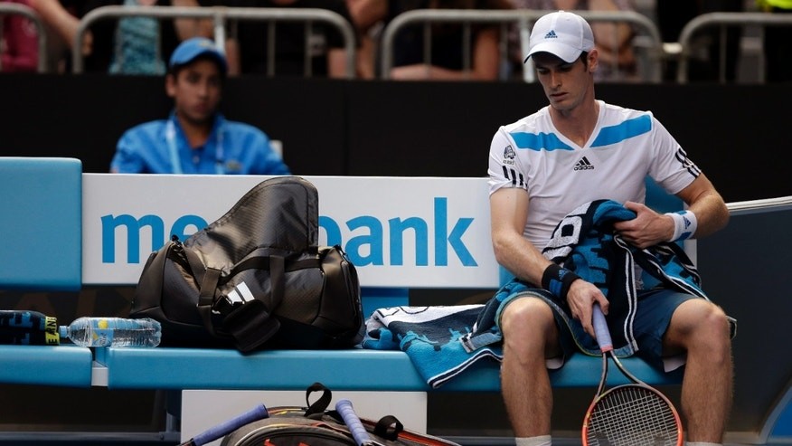Andy Murray of Britain sits in a chair beside his smashed racket during a break in his fourth round match against Stephane Robert of France at the Australian Open tennis championship in Melbourne, Australia, Monday, Jan. 20, 2014.(AP Photo/Rick Rycroft)