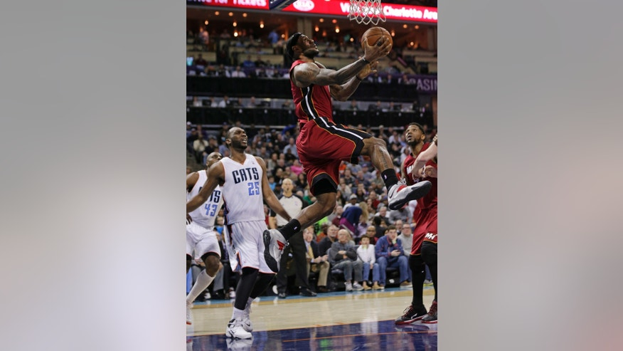 Miami Heat's LeBron James, top, drives past Charlotte Bobcats' Al Jefferson, left, during the second half of an NBA basketball game in Charlotte, N.C., Saturday, Jan. 18, 2014. The Heat won 104-96 in overtime. (AP Photo/Chuck Burton)
