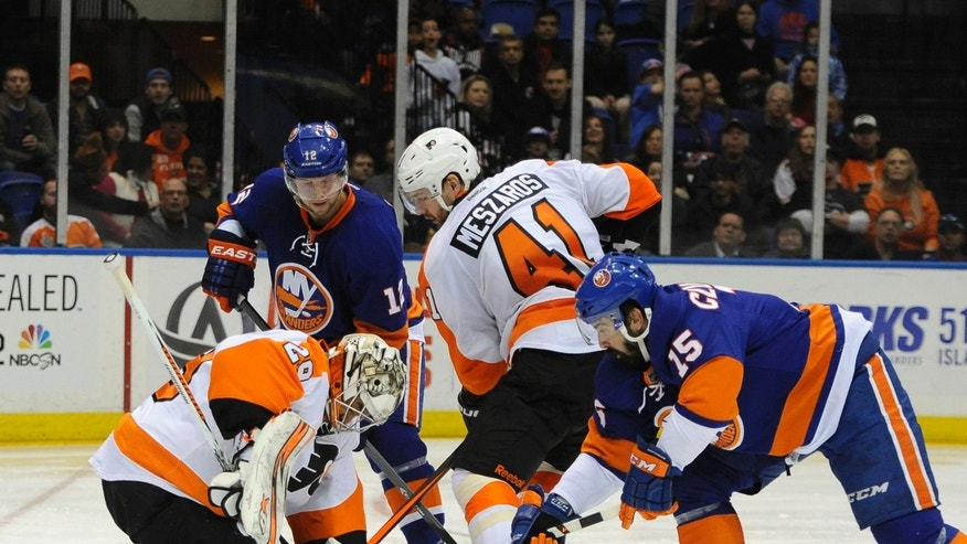 Philadelphia Flyers goalie Ray Emery (29) and Andrej Meszaros (41) defend against New York Islanders' Josh Bailey (12) and Cal Clutterbuck (15) in the second period of an NHL hockey game on Monday, Jan. 20, 2014, in Uniondale, N.Y. (AP Photo/Kathy Kmonicek)