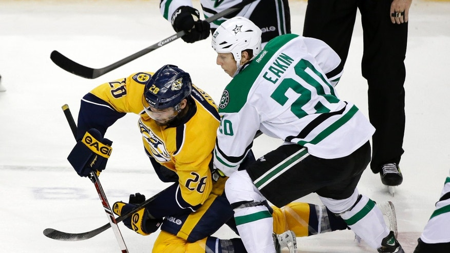 Nashville Predators forward Paul Gaustad (28) passes the puck away from Dallas Stars center Cody Eakin (20) in the second period of an NHL hockey game Monday, Jan. 20, 2014, in Nashville, Tenn. (AP Photo/Mark Humphrey)