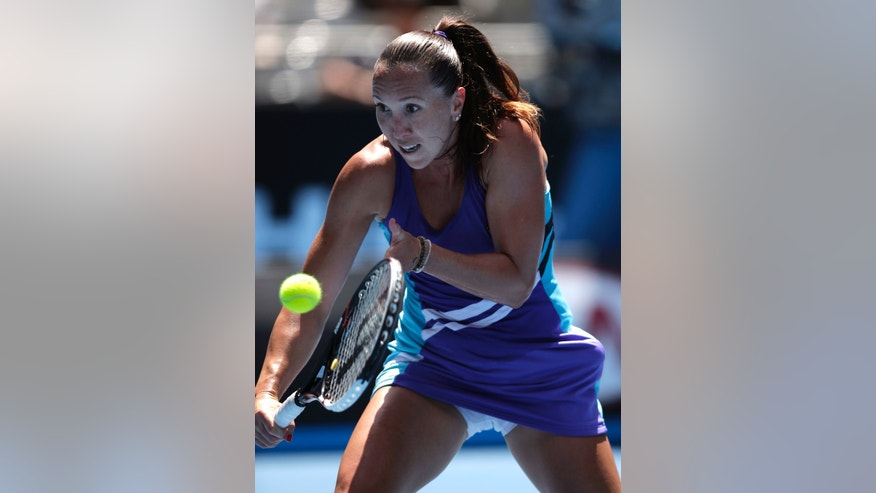 Jelena Jankovic of Serbia makes a backhand return to Simona Halep of Romania during their fourth round match at the Australian Open tennis championship in Melbourne, Australia, Monday, Jan. 20, 2014.(AP Photo/Rick Rycroft)
