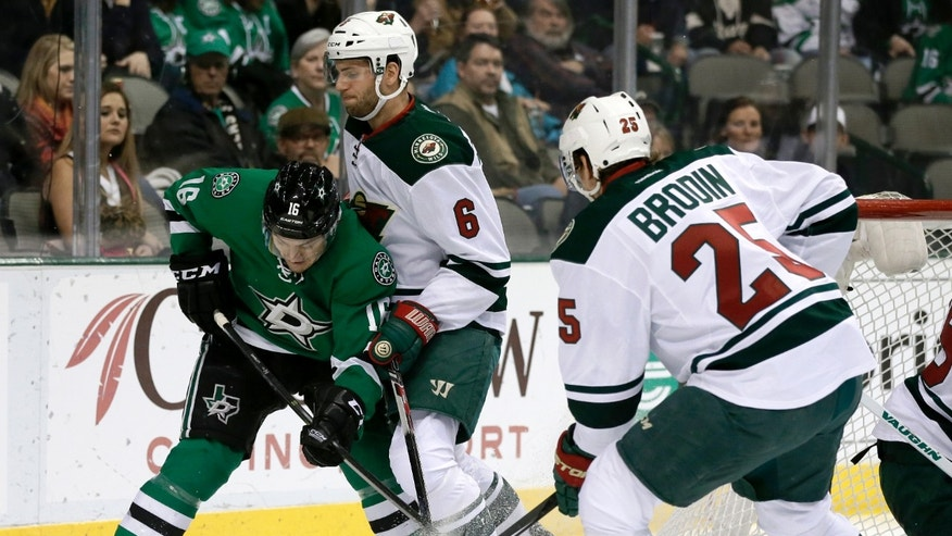 Dallas Stars' Shawn Horcoff (10) fights Minnesota Wild defenseman Marco Scandella (6) and defenseman Jonas Brodin (25) for control of the puck in the first period of an NHL hockey game, Tuesday, Jan. 21, 2014, in Dallas. (AP Photo/Tony Gutierrez)