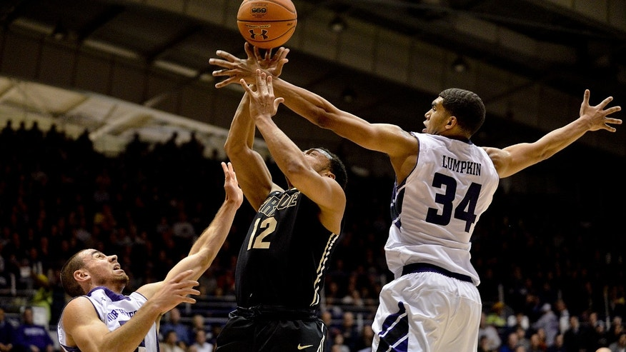 Northwestern guard Tre Demps (14) and Northwestern guard/forward Sanjay Lumpkin (34) blocks Purdue guard Bryson Scott (12) during the first half of an NCAA college basketball game in Evanston, Ill., on Tuesday, Jan. 21, 2014. (AP Photo/Matt Marton)
