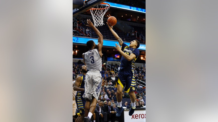 Marquette forward Juan Anderson (10)  shoots over Georgetown forward Mikael Hopkins (3) during the first half of an NCAA college basketball game, Monday, Jan. 20, 2014, in Washington. (AP Photo/Alex Brandon)