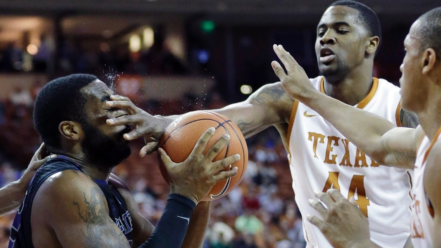 Kansas State's Thomas Gipson, left, takes a foul to the face from Texas' Prince Ibeh (44)during the second half of a NCAA college basketball game, Tuesday,  Jan. 21, 2014, in Austin, Texas. Texas won 67-64. (AP Photo/Eric Gay)