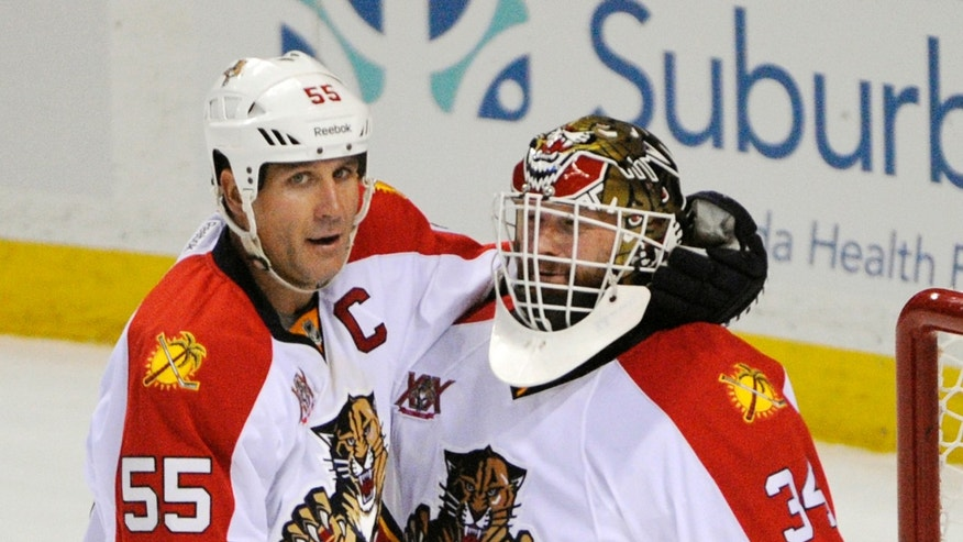 Florida Panthers' Ed Jovanovski (55) celebrates with goaltender Tim Thomas (34) after defeating the Buffalo Sabres during an NHL hockey game in Buffalo, N.Y., Tuesday, Jan. 21, 2014.  Florida won 4-3. (AP Photo/Gary Wiepert)