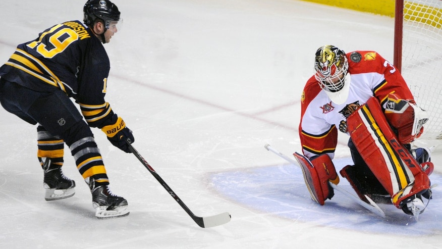 Buffalo Sabres center Cody Hodgson (19) gets stopped by Florida Panthers goaltender Tim Thomas (34) as he makes a shoulder save during the third period of an NHL hockey game in Buffalo, N.Y., Tuesday, Jan. 21, 2014. Florida won 4-3. (AP Photo/Gary Wiepert)