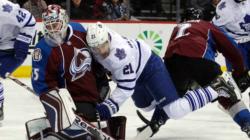 Toronto Maple Leafs left wing James van Riemsdyk (21) collides wight Colorado Avalanche goalie Jean-Sebastien Giguere (35) as Maple Leafs right wing Phil Kessel (81), not shown, scored a goal during the second period of an NHL game in Denver on Tuesday, Jan. 21, 2014. (AP Photo/Joe Mahoney)