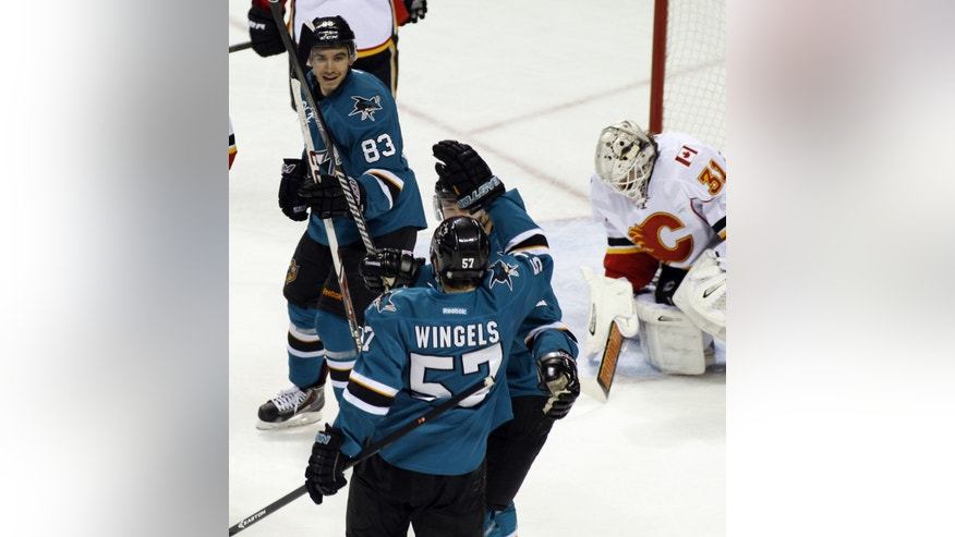 San Jose Sharks' Tommy Wingels (57), front, celebrates with teammates Patrick Marleau, center, and Matt Nieto (83) after scoring past Calgary Flames goalie Karri Ramo, far right, during the first period of an NHL hockey game, Monday, Jan. 20, 2014, in San Jose, Calif.  (AP Photo/George Nikitin)