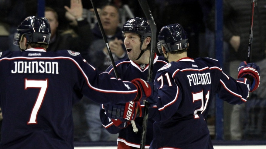 Columbus Blue Jackets' R.J. Umberger, center, celebrates his goal against the Los Angeles Kings with teammates Jack Johnson, left, and Nick Foligno in the first period of an NHL hockey game in Columbus, Ohio, Tuesday, Jan. 21, 2014. The Blue Jackets won 5-3. (AP Photo/Paul Vernon)