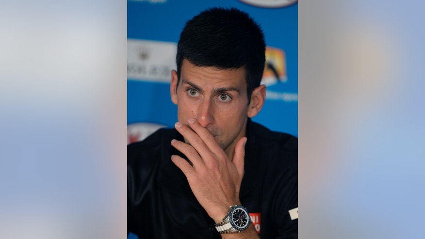 Novak Djokovic of Serbia gestures at a press conference following his quarterfinal loss to Stanislas Wawrinka of Switzerland at the Australian Open tennis championship in Melbourne, Australia, Tuesday, Jan. 21, 2014. (AP Photo/Andrew Brownbill)